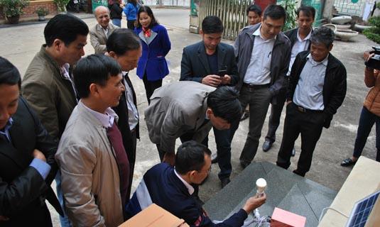 Cán bộ kỹ thuật của sở Công thương hướng dẫn bà con và cán bộ xã Đồng Nghê thao tác lắp đặt và sử dụng máy phát điện mặt trời Sola của công ty Vũ Phong trao tặng.