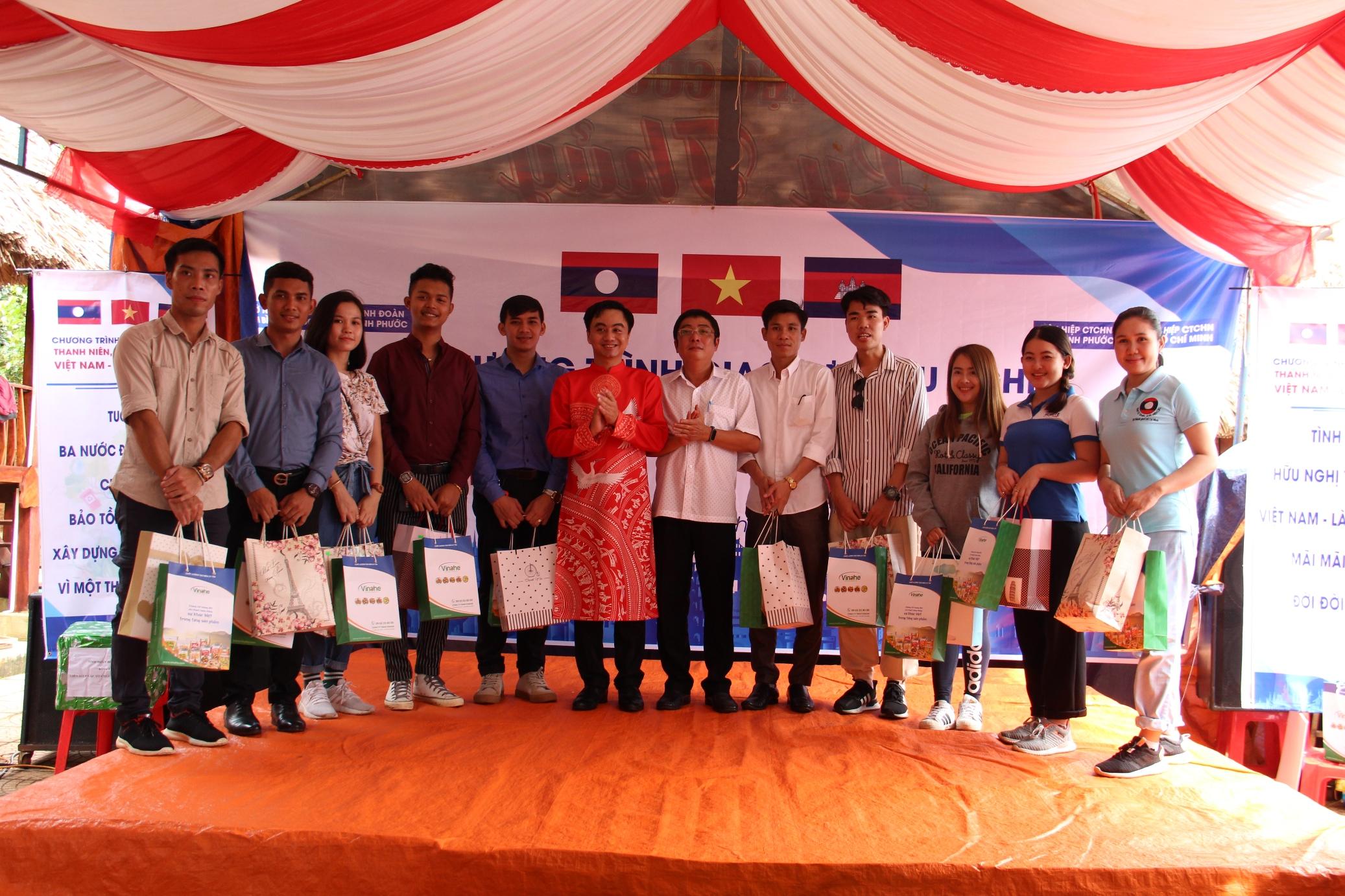 Bí thư Tỉnh Đoàn Trần Quốc Duy (mặc áo dài đỏ) và Phó Giám đốc Sở Ngoại vụ tỉnh Bình Phước tỉnh Bình Phước Bùi Quốc Khánh (thứ sáu từ phải qua) tặng quà cho sinh viên Campuchia và Lào